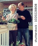 Small photo of Elderly positive woman talking with male neighbor at balcon