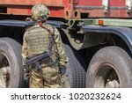 german female soldier stands in front of a truck trailer