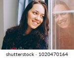 young woman sitting on window... | Shutterstock . vector #1020470164