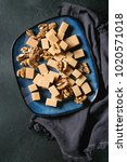 Small photo of Salted caramel fudge candy served on blue ceramic plate with caramelized walnuts on textile napkin over black texture background. Top view, space. Dessert set