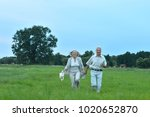 senior couple running in field | Shutterstock . vector #1020652870