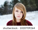 Small photo of blond girl with a bangs bangs in a red sweater stands in a snowy forest