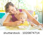 mom feed cute young child | Shutterstock . vector #1020874714