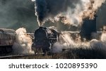Steam train locomotive approaching a station passing through a goods yard letting of smoke and steam lit from behind creating atmospheric photograph