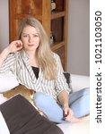 caucasian woman in a living room | Shutterstock . vector #1021103050