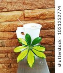 Small photo of White coffee cup and yellow-green leaves. It is placed on an aluminum balcony rail, adjacent to the wall.