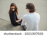 Stock photo shy girl sitting on a wall with boyfriend and smiling while he is flirting with her 1021307020