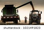 pouring corn grain into tractor ... | Shutterstock . vector #1021491823
