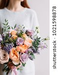 Small photo of Very nice young woman holding big and beautiful colourful flower wedding bouquet with purple carnations and mattiolas, cream David Austin roses, ranunculus and pistachios