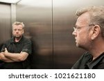 Small photo of Man in the elevator looking at himself skeptically in the mirror