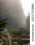 Small photo of A lone trekker passing a rock gorge with steep walls while hiking on Table Mountain of Cape Town