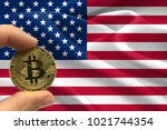 hand holding bitcoin on united... | Shutterstock . vector #1021744354