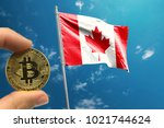 hand holding bitcoin on canada... | Shutterstock . vector #1021744624