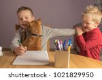 two brothers play with a dog... | Shutterstock . vector #1021829950