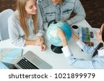 young couple in a tour agency... | Shutterstock . vector #1021899979