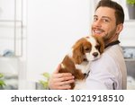 Stock photo horizontal shot of a handsome cheerful young male veterinarian smiling to the camera holding an 1021918510