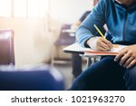 Small photo of soft focus.high school or university student holding pencil writing on paper answer sheet.sitting on lecture chair taking final exam attending in examination room or classroom.student in uniform