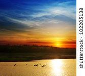 dramatic sunset over river with swans - stock photo