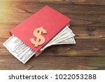 book  dollars on a wooden...   Shutterstock . vector #1022053288