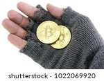 Small photo of bankrupt concept: hand of the poor with broken glove with two golden bitcoin coins