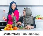 two muslim woman in kitchen... | Shutterstock . vector #1022084368
