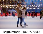 Small photo of Theme ice skating rink and loving couple. meeting young, stylish people ride by hand in crowd on city skating rink lit by light bulbs and lights. Ice skating in winter for Christmas on ice arena.