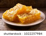 honeycombs on a plate on wooden ... | Shutterstock . vector #1022257984