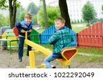 funny boys swing on a yellow... | Shutterstock . vector #1022292049