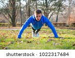 young male runner doing push up ... | Shutterstock . vector #1022317684