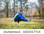 young male runner stretching in ... | Shutterstock . vector #1022317714