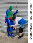 Small photo of London, UK - May 28 2017 : Cosplayer having a costume adjustment at the London Comic Con 2017