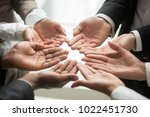 Small photo of Diverse multi-ethnic business team members join helping hands group together palms up as concept of involvement, contribution in common goal, supporting unity and crowdfunding donation, close up view
