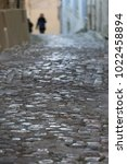 Small photo of View from bellow of a narrow alley in on old city in France. Paved street with house walls on each side. Two unidentified blur dark silhouettes at the end of the leading line. Rough surface pavement.