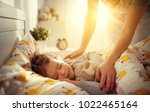 mother wakes up sleeping child... | Shutterstock . vector #1022465164