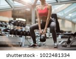 fit young woman squatting while ...   Shutterstock . vector #1022481334