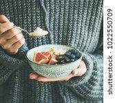 healthy winter breakfast. woman ... | Shutterstock . vector #1022550709