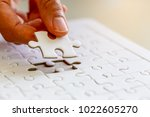 Small photo of Woman's hand placing put the last white jigsaw puzzle piece to complete the mission, business success concept