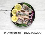 Stock photo herring fillet with salt pepper herbs onion and lemon on black plate on white background top 1022606200