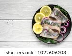 Stock photo marinated herring fillet with pepper herbs onion and lemon on black plate on white background 1022606203