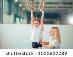 mother helping her daughter to... | Shutterstock . vector #1022622289