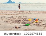 Happy boy playing beach toy and splashing in the sea beach. Kids having fun outdoors. Summer vacation and healthy lifestyle concept.