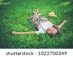 young woman lying down on grass.... | Shutterstock . vector #1022700349