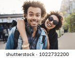 Small photo of Outdoor protrait of african-american couple hugging and smiling broadly at camera while walking in park and expressing positive emotions. Brother and sister finally got along and spend time together