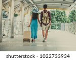 Small photo of Couple of lovers with valise walking in the town or terminal.Tourism, Travel, Lover, leisure and Teenage concept.
