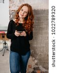 Small photo of Pretty slender redhead woman smiling at the camera with an amused friendly look while leaning against a brisk wall indoors