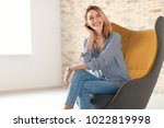 young woman sitting in armchair ... | Shutterstock . vector #1022819998