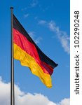 german national flag blowing in the wind against blue sky - stock photo