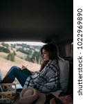 Small photo of Woman vacationer enjoying picnic in car trunk and twriting in notebook.