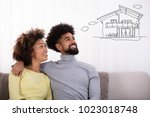 happy couple sitting on sofa... | Shutterstock . vector #1023018748