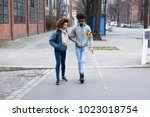 young woman helping blind man... | Shutterstock . vector #1023018754